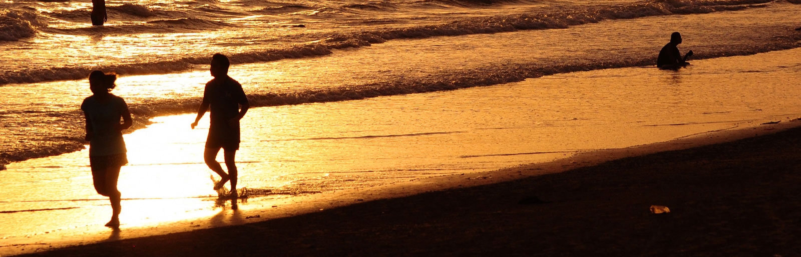 people enjoying waves rolling in on a beach with the sunset reflecting off the water