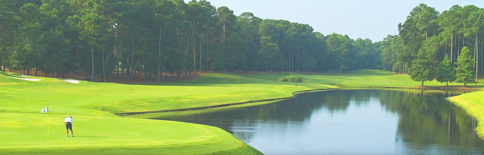 Golf course fairway, the green, a large pond, surrounded by trees on a partly cloudy summer day